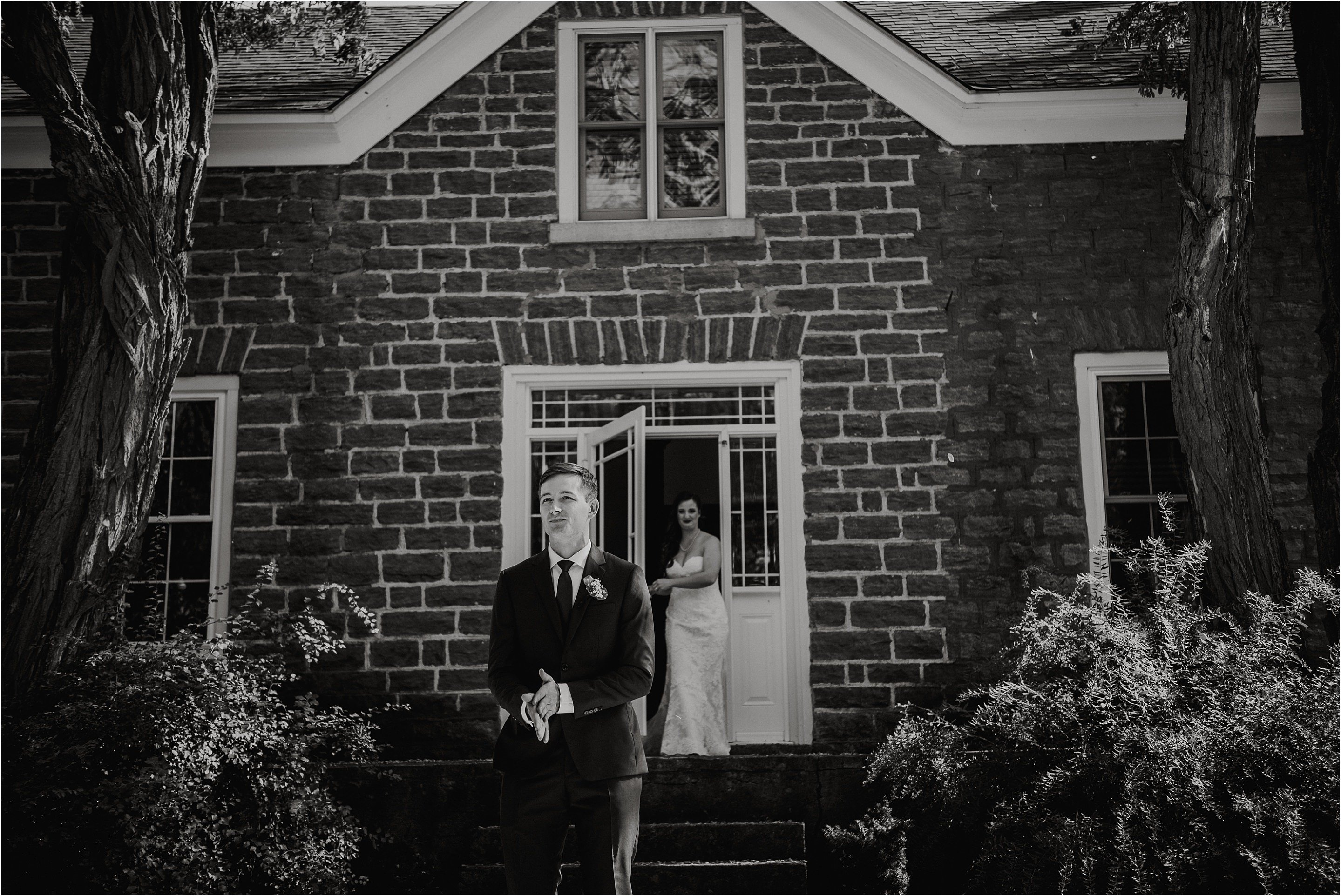 The groom waiting to have his first look at his bride in front of the farm house at Stonefields Estate. Photo by Cindy Lottes Photography
