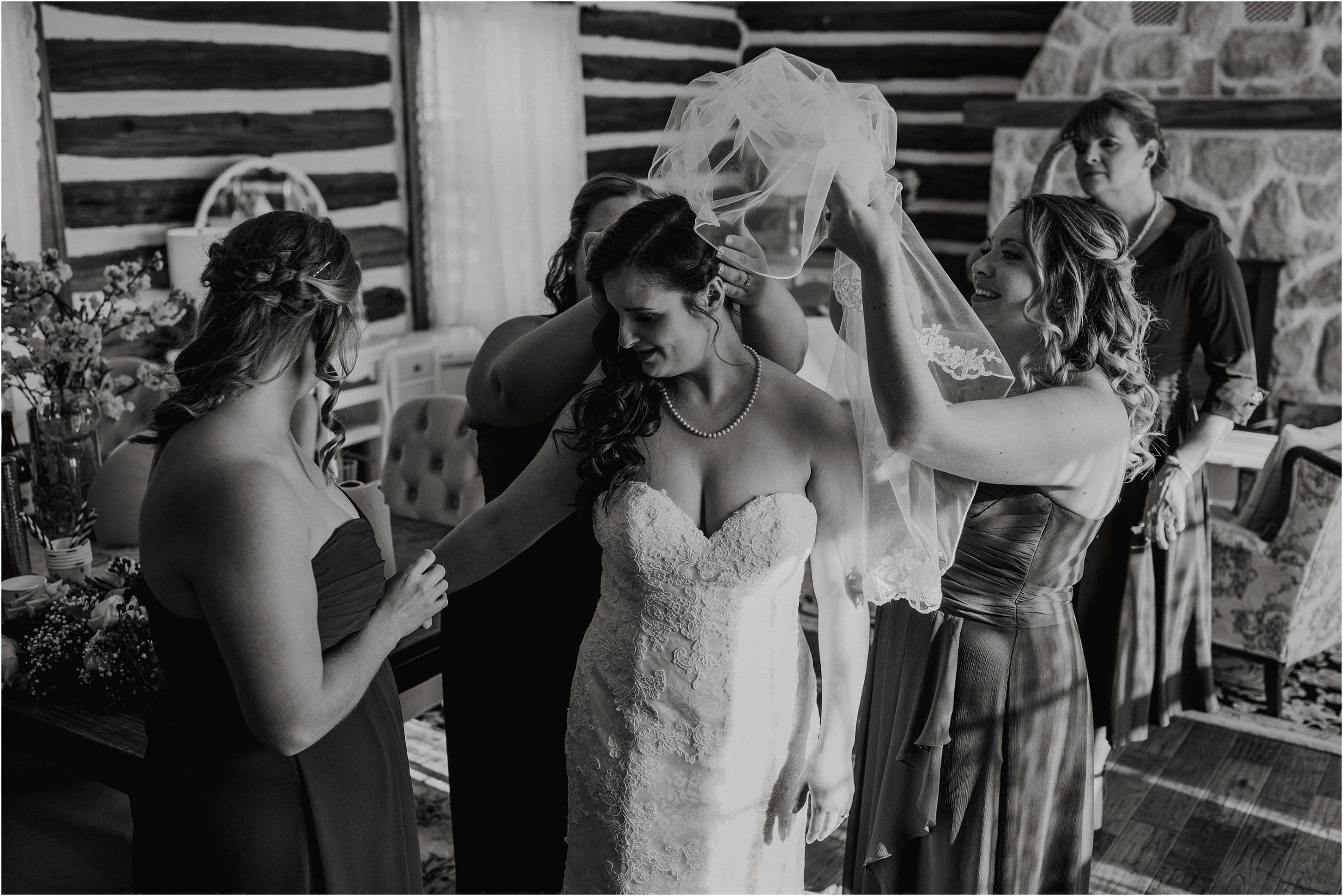 Bridesmaids help place the veil on the bride's head. Photo by Cindy Lottes Photography