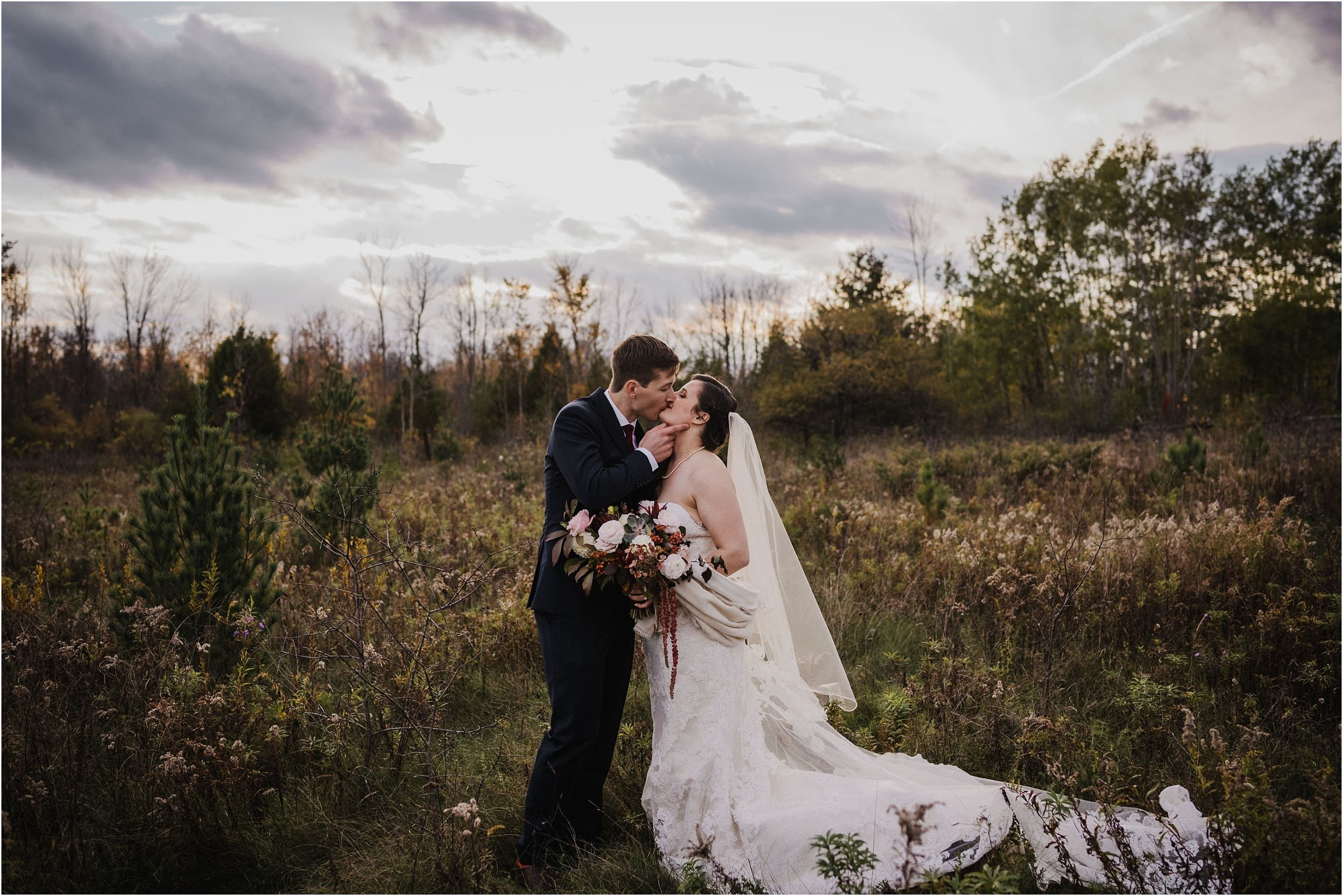 A romantic portrait of a bride and groom kissing at sunset in a field of wildflowers at Stonefields.