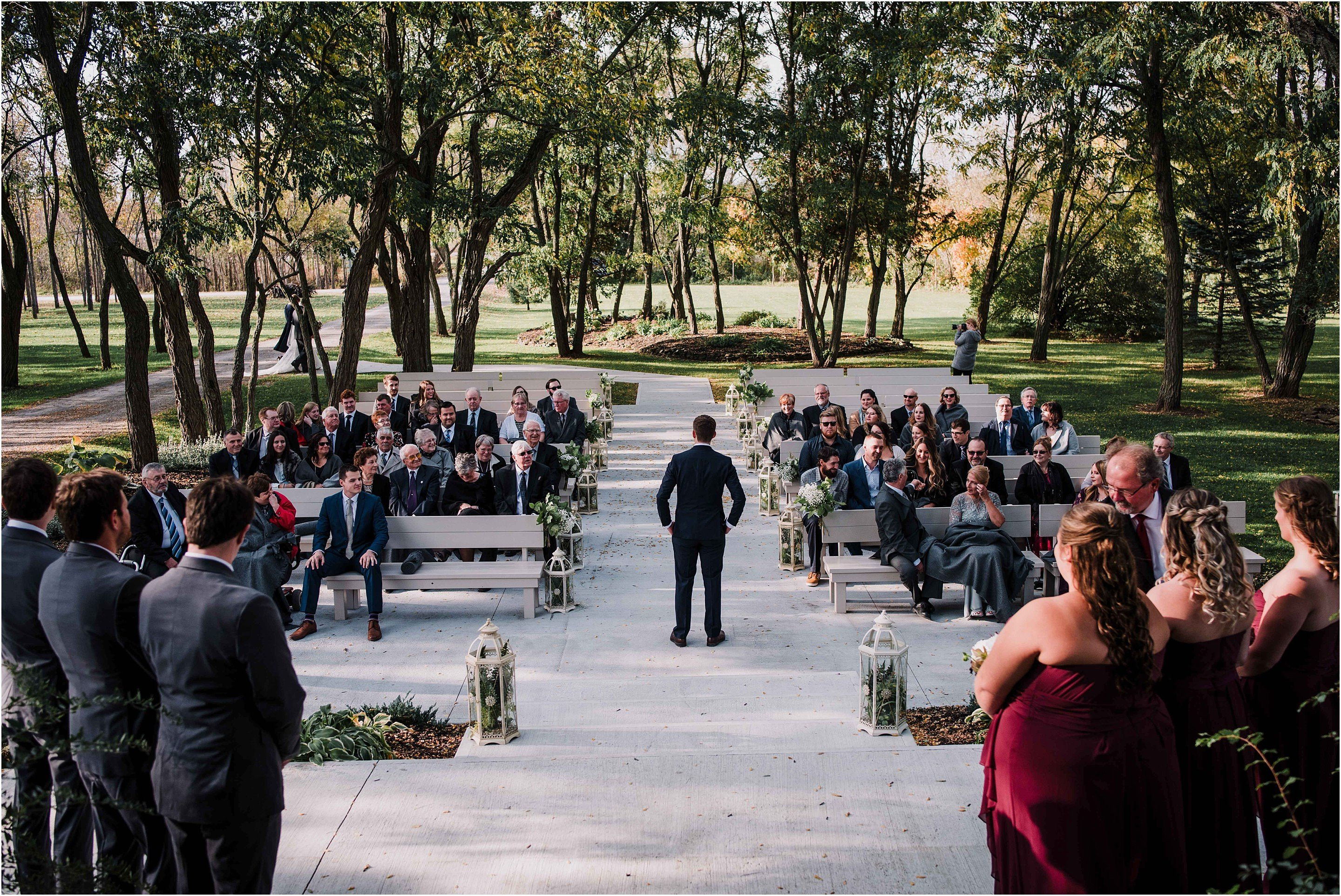 The groom waiting for his bride at the outdoor alter at Stonefields. Photo by Cindy Lottes Photography