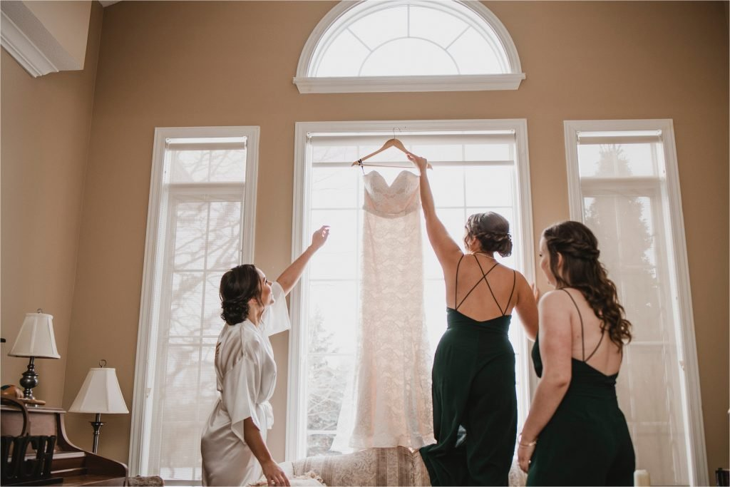 bridesmaid takes down dress for bride