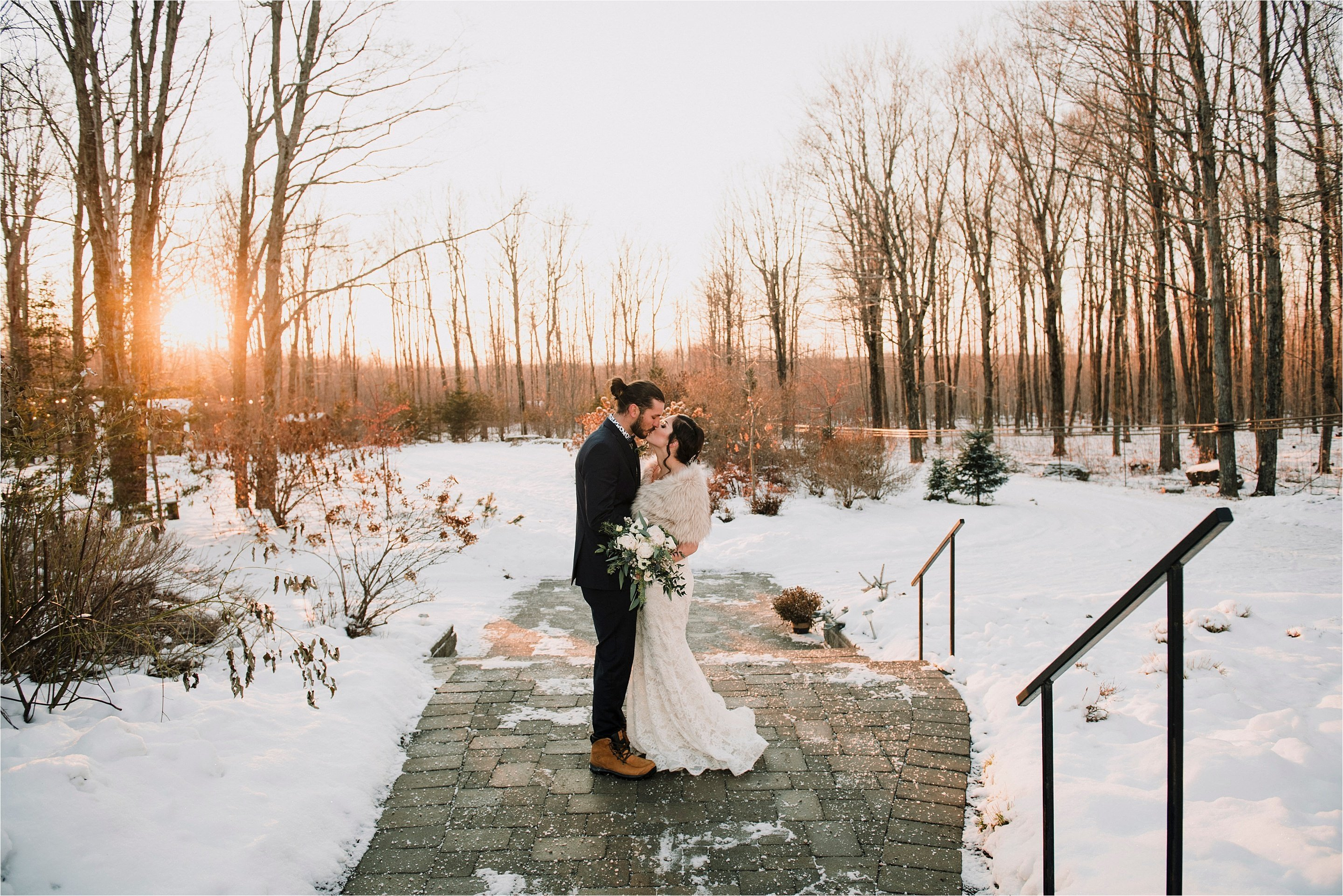 bride and groom kiss outside in the snow