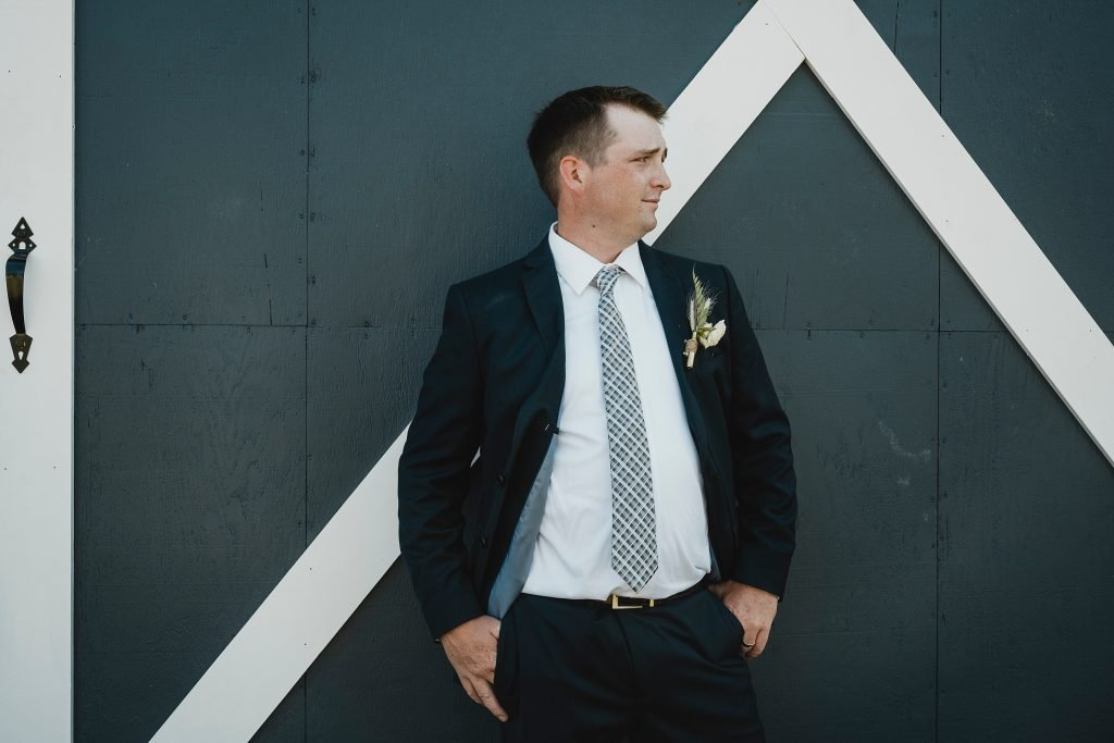 groom portraits in front of barn