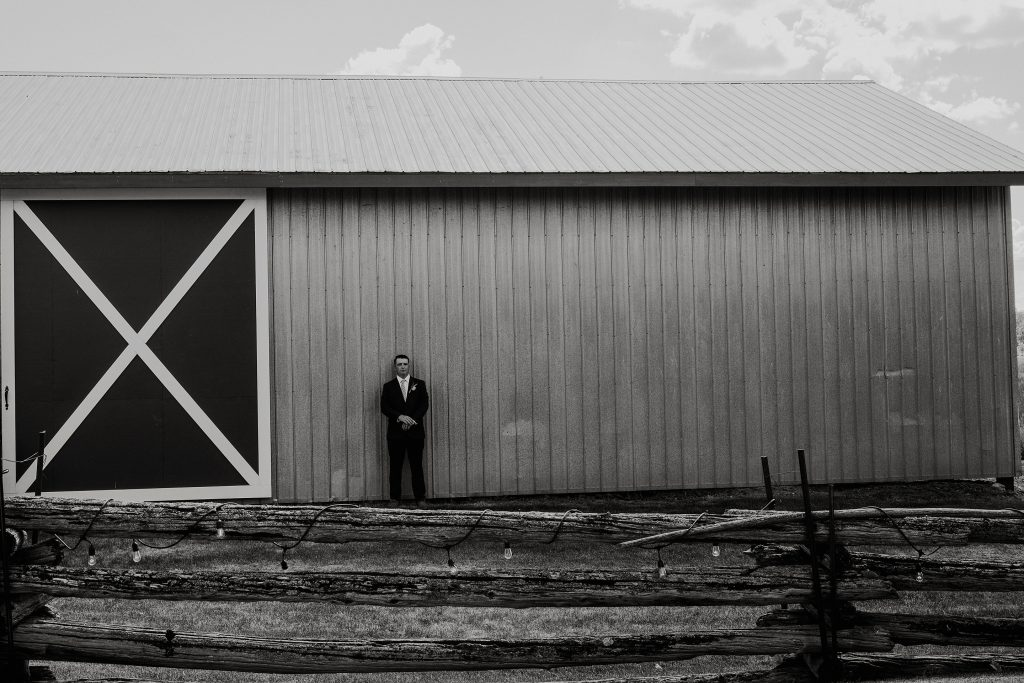 groom portrait in front of the barn