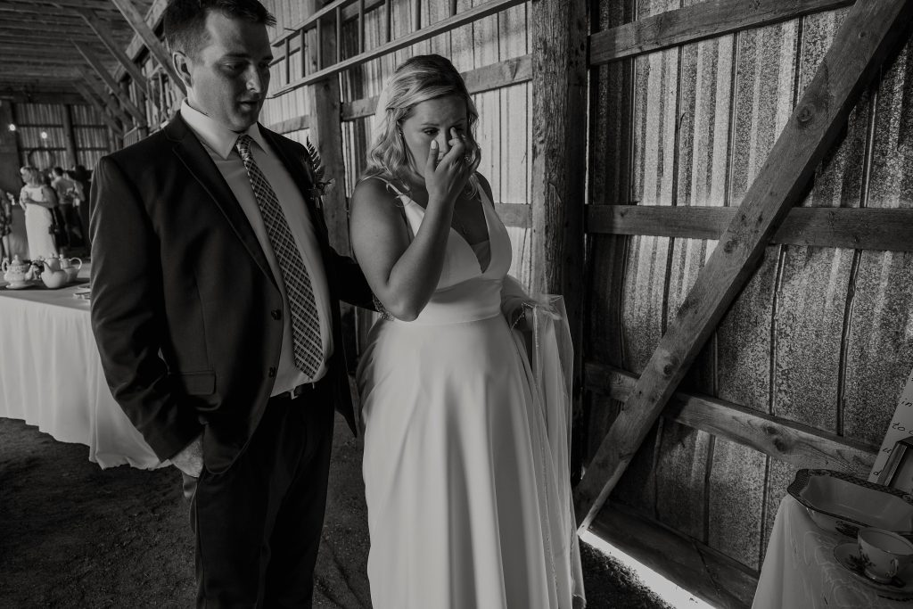 Couple getting emotional at viewing grandparents portraits - Dunrobin Intimate Backyard Farm Wedding