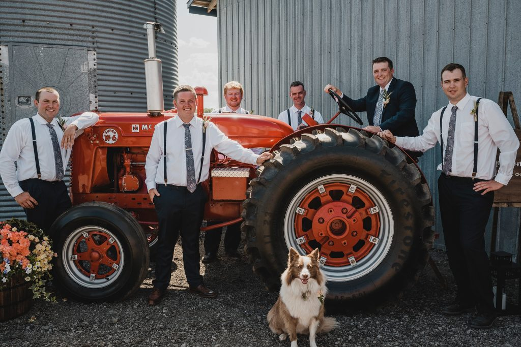 groomsmen posing in front of a vintage tractor