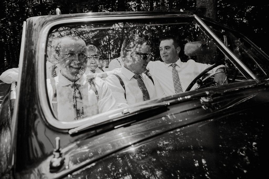 groomsmen in vintage car on wedding day