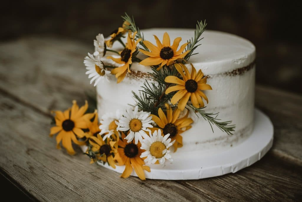 Simple wedding cake decorated with wildflowers