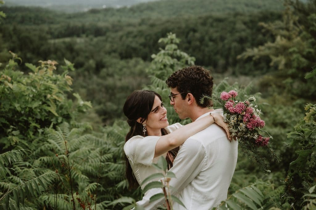 Bride and Groom embrace in front of a mountain at Le Belvedere in Wakefield Quebec
