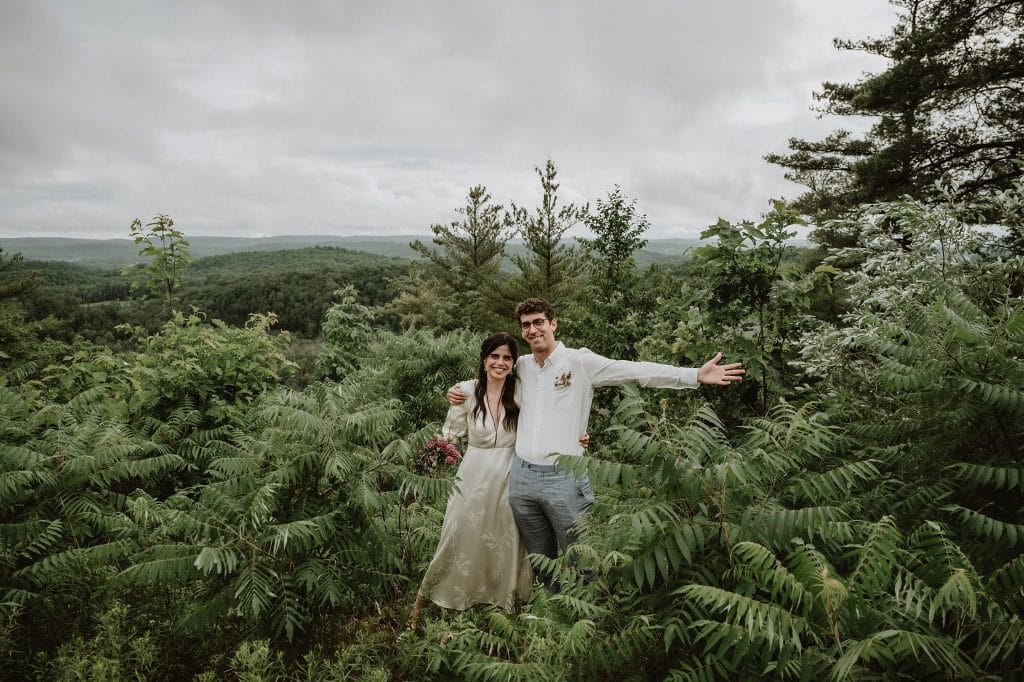 Bride and Groom happily pose for a picture in front of the mountains at Le Belvedere in Wakefield Quebec
