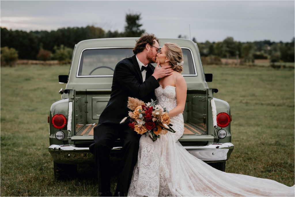 Bride and Groom kiss in the back of a vintage pickup truck in a field in Pembroke