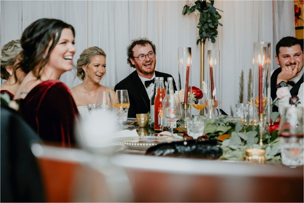 Bride and Groom laugh during speeches at their wedding reception at Grey Gables Inn in Pembroke