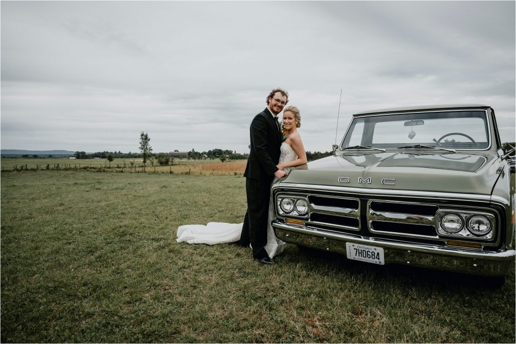 Bride and groom pose in front of vintage truck in Pembroke
