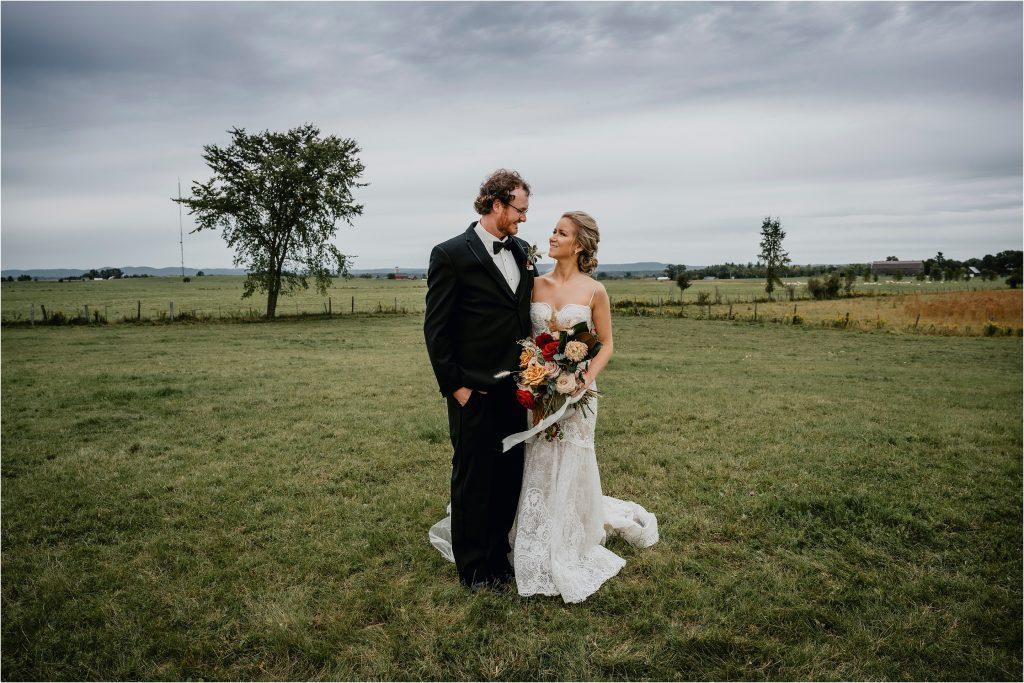 Bride and Groom pose in a farm field in Pembroke