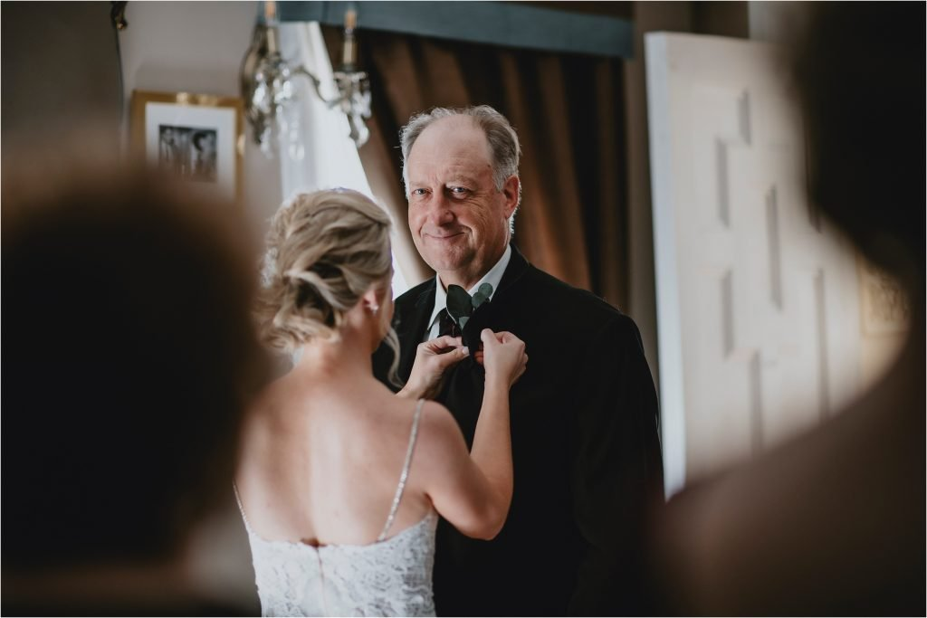 Bride placing her Dad's Boutonniere in Grey Gables Inn in Pembroke