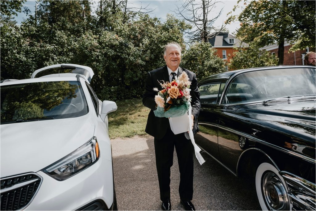 Father of the Bride carrying flowers into Grey Gables Inn in Pembroke