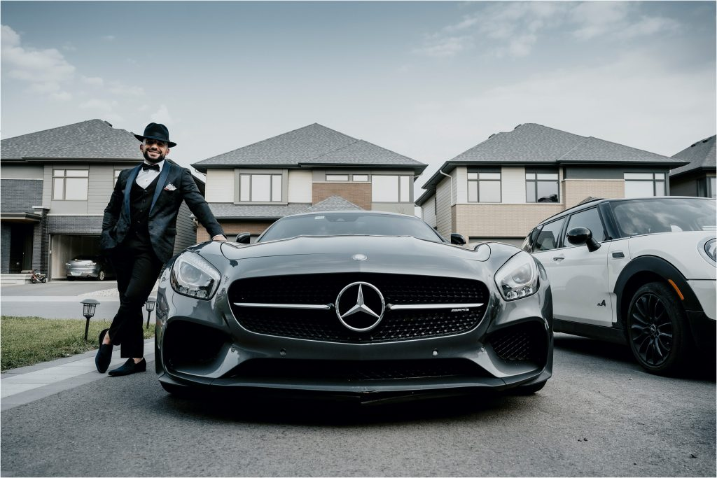 Groom poses in front of a Mercedes sports car.