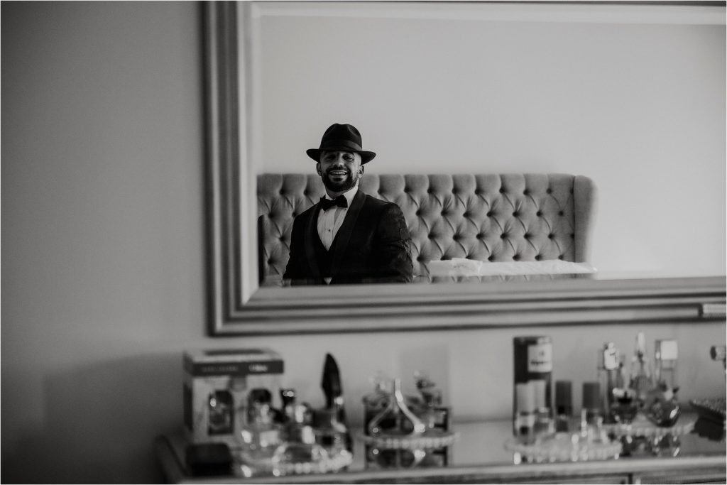 Groom looks at his reflection in the mirror.