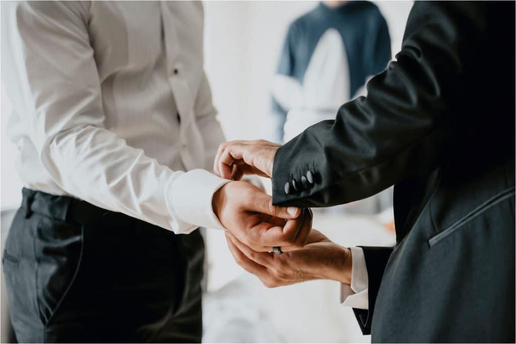 Best man helps groom in to his suit.