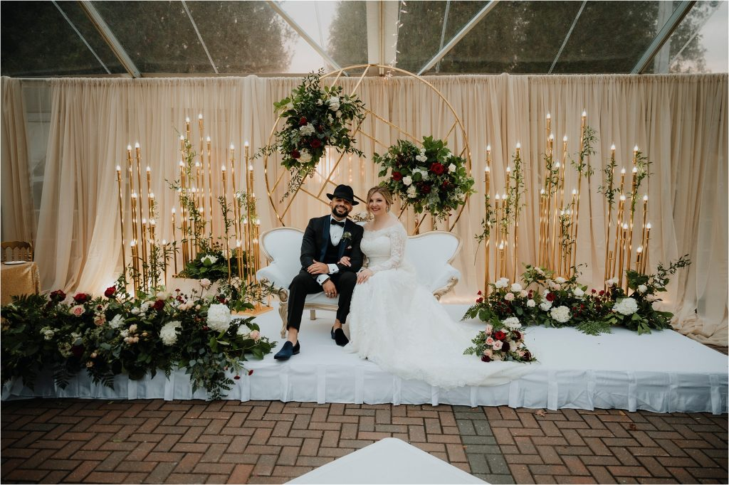 Bride and groom pose for a portrait in their wedding tent at Orchard View