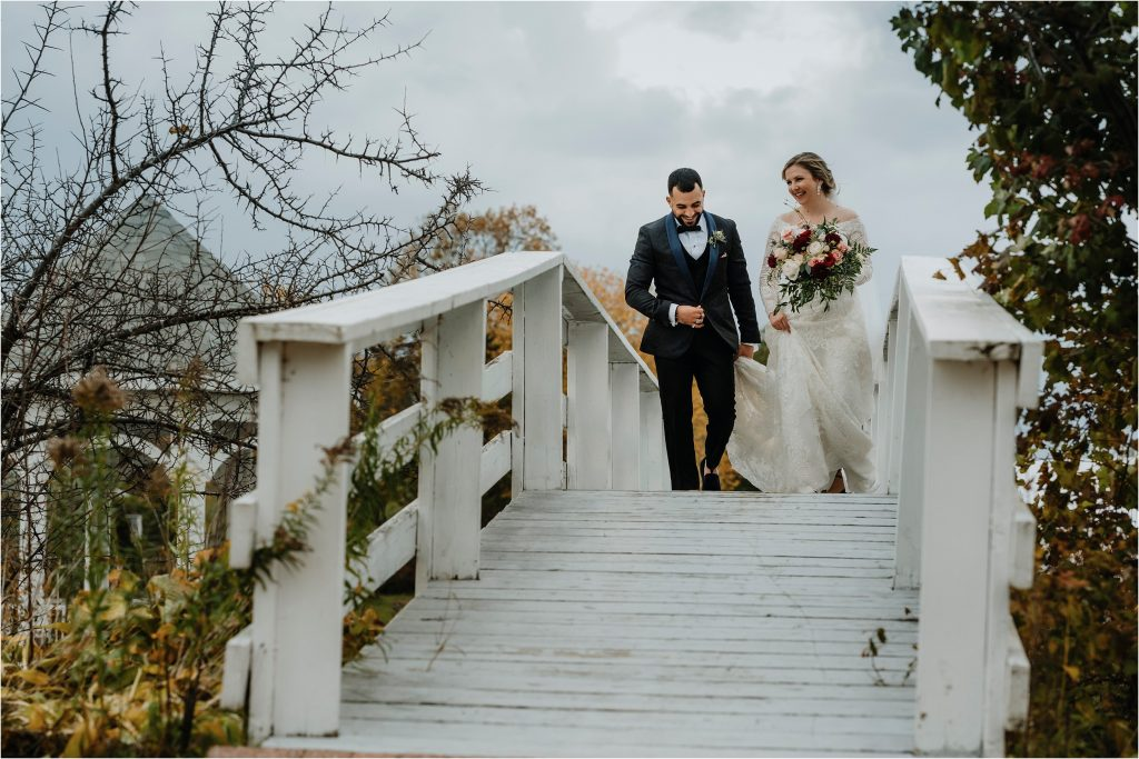 Bride and Groom walk down the white bridge at Orchard View