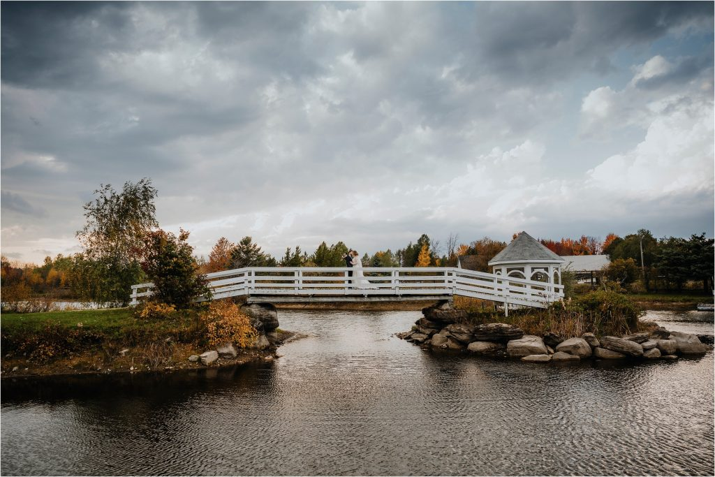 Bride and Groom kiss on white bridge at Orchard View Weddings and Events