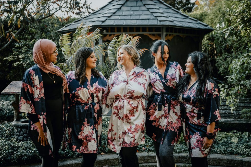 bride and her bridesmaids smile for a picture in her backyard