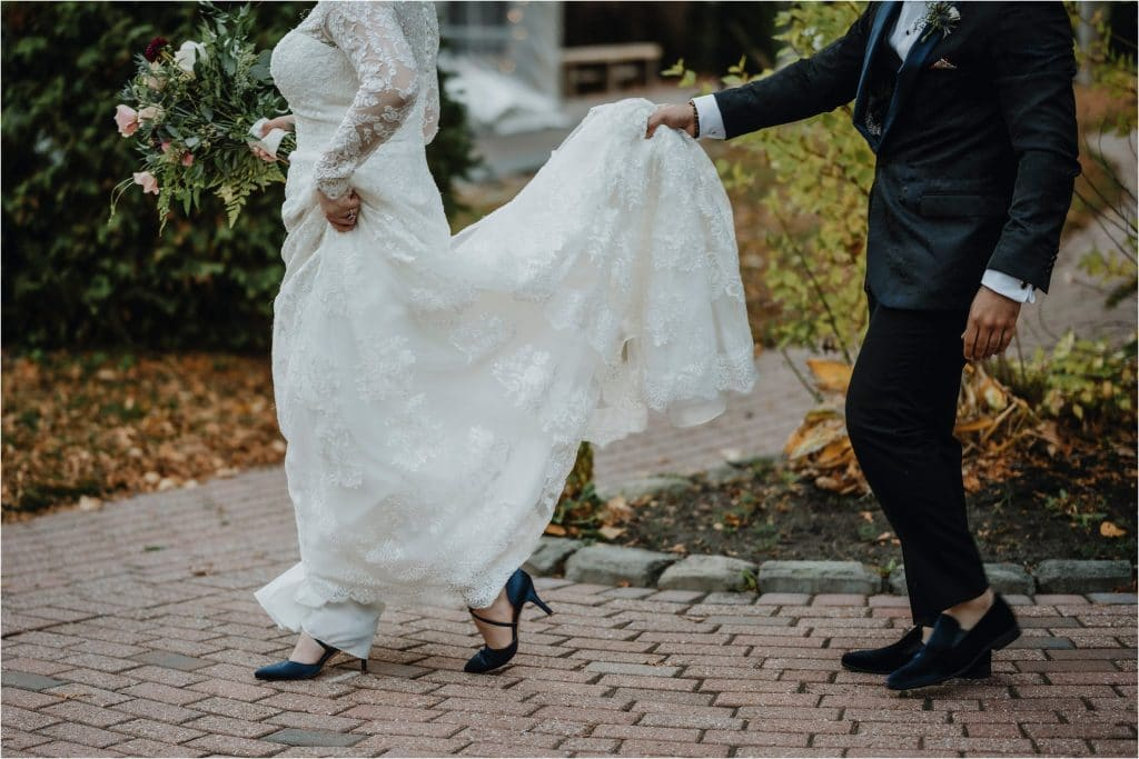 bride and groom walk with their blue shoes on