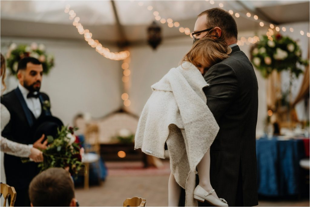 dad carries tired flower girl at orchard view wedding