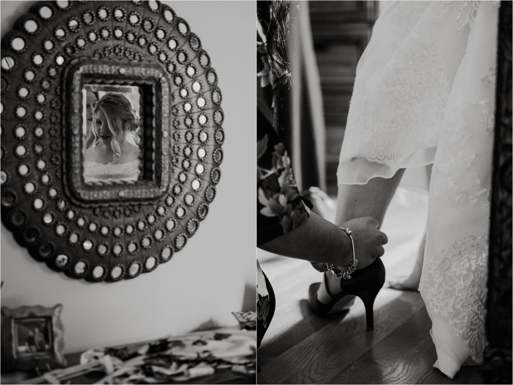 bride's reflection in the mirror and bridesmaid fastens her high heel shoe.
