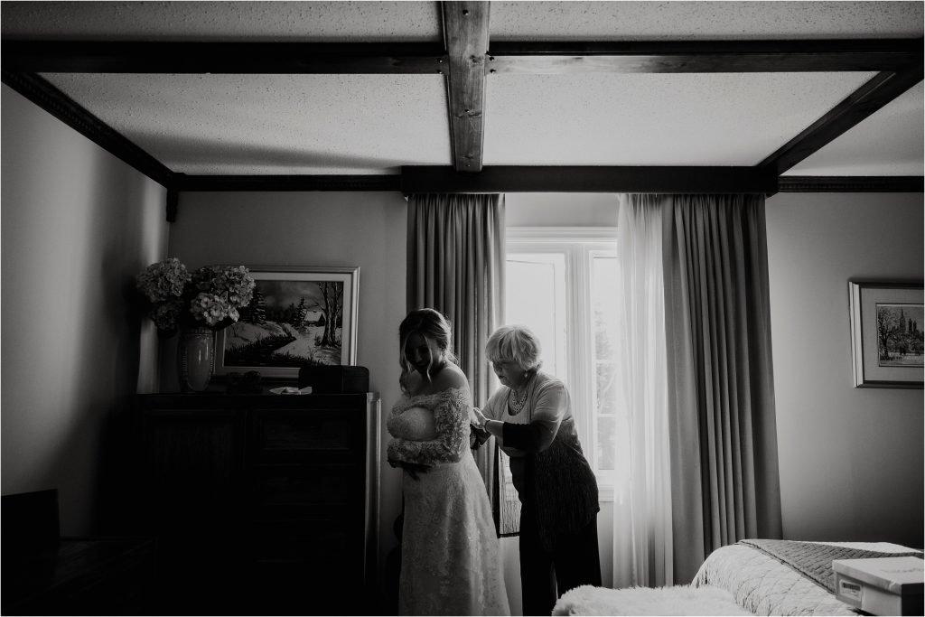 bride's mom fastens up her dress