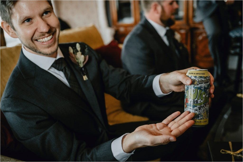 a groomsmen shows off his can of beer