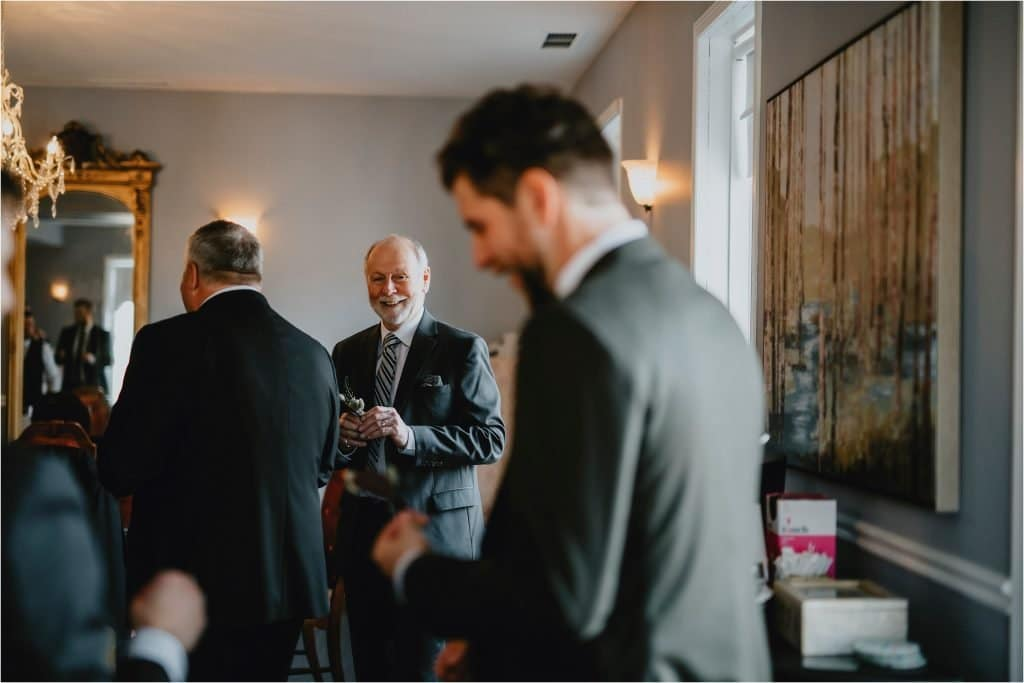 father of the groom gives him a big smile at the grand hotel