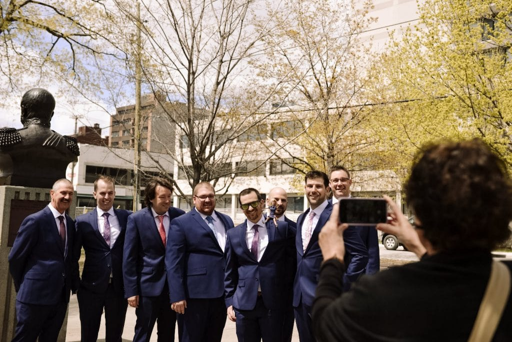 A passerby takes  a photo of the groom and the groomsmen on the streets of Ottawa.