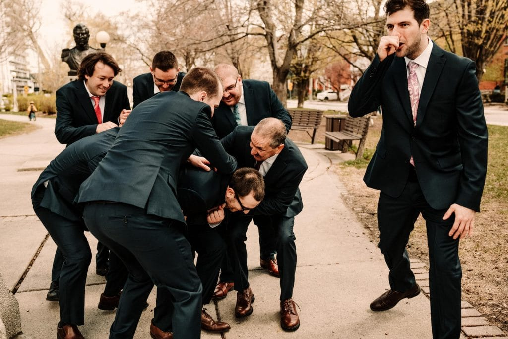 A groomsman pretends to be a secret agent while the rest of the guy tackle the groom in this fun portrait before his wedding ceremony.