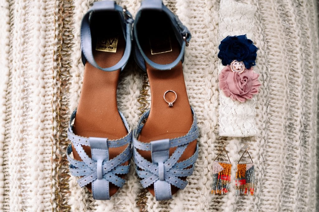 A pair of fancy blue sandals and colourful earrings and an engagement ring.