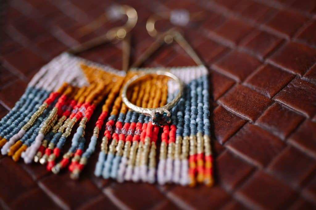 A bride's blue engagement ring sitting on a pair of colourful earrings from Lost Thread Weaving.
