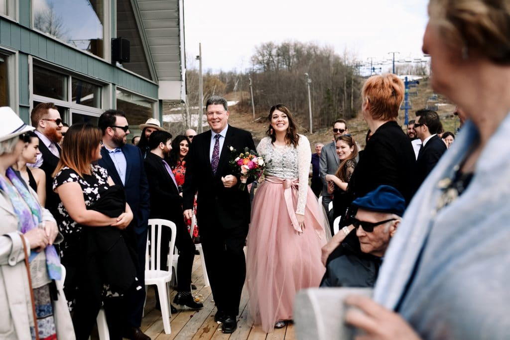 The bride smiles as her father walks her down the aisle at Camp Fortune Ski Resort.