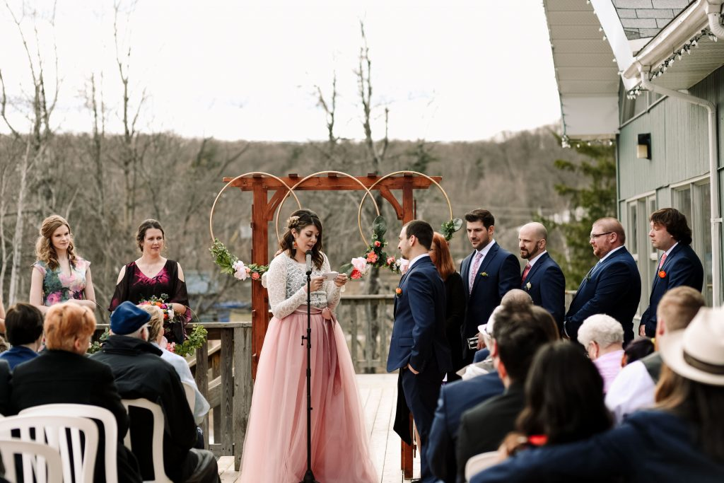 The bride reads her vows to the groom in front of the Gatineau Hills in a beautiful relaxed outdoor wedding ceremony.