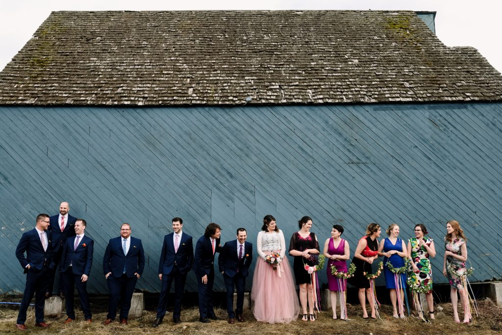 A wedding party stands side by side, laughing at each other in front of a big blue building.