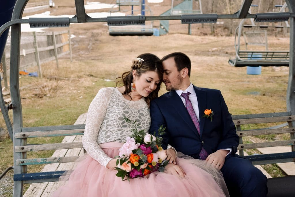 The bride and groom snuggle up while sitting on the ski chair lift at Camp Fortune.