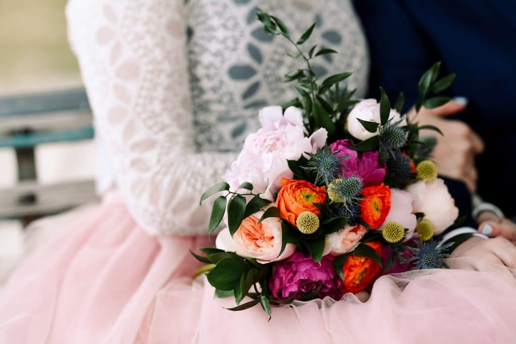 A colourful wedding day bouquet with pink peonies, blue sea holly's, and flowing greenery.