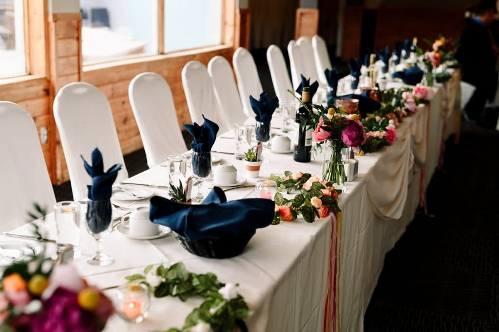 The head table inside the lodge at Camp Fortune, decorated with white linens, blue napkins and colourful fresh flowers.