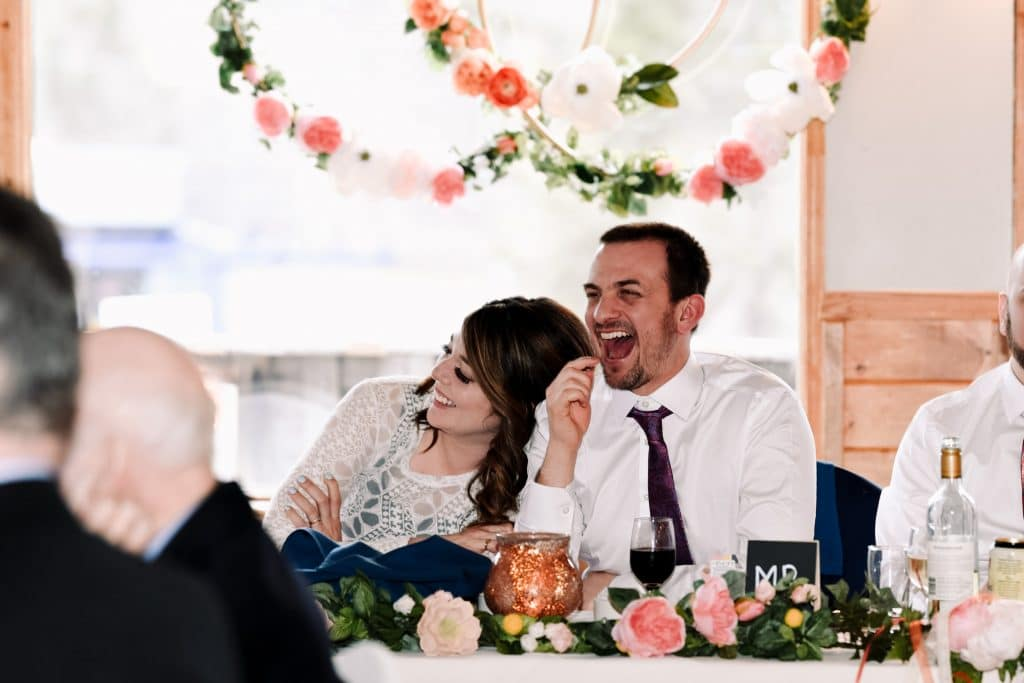 The bride leans on the groom while laughing at one of her guests speeches during the reception at Camp Fortune.
