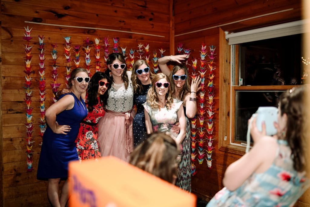 The bride and her bridesmaids pose for a polaroid picture in front of a wall of colourful origami swans.