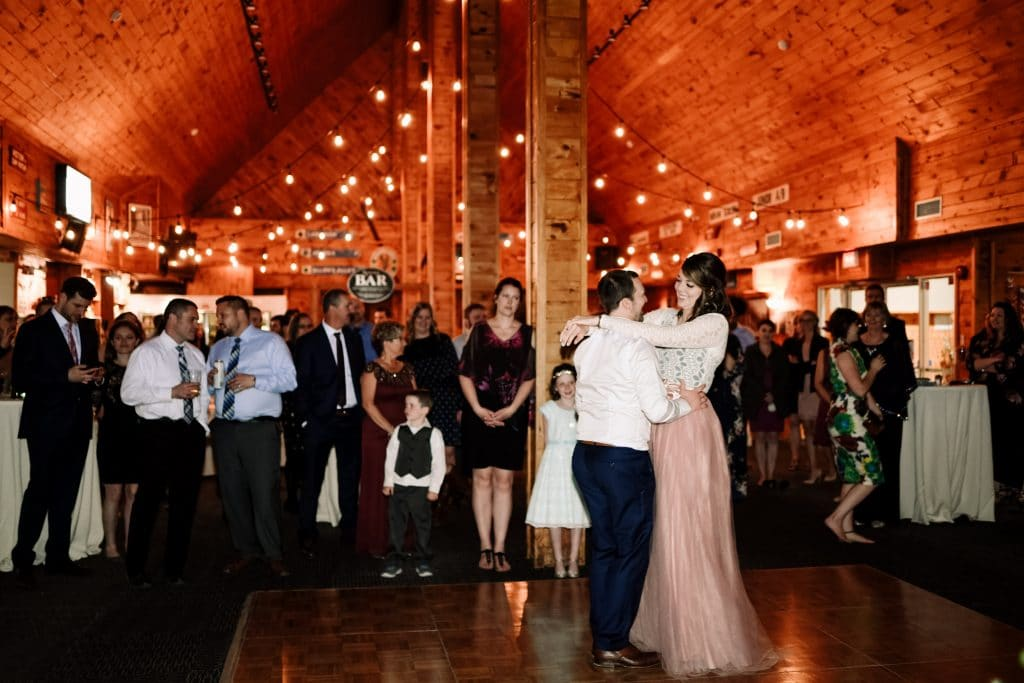 The bride smiles at her groom during the first dance under string lights inside the lodge at Camp Fortune Ski Hill.