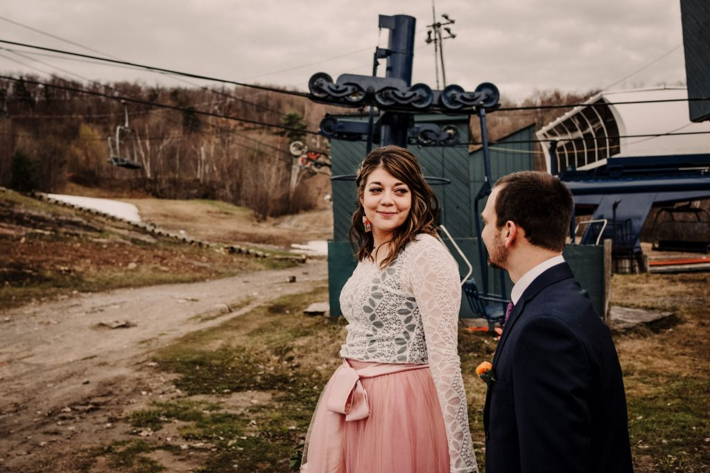 The bride looks back at her groom with a big smile as they walk hand in hand in front of the chair lift at Camp Fortune.